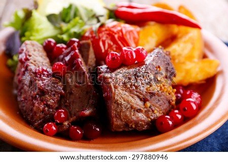 Tasty roasted meat with cranberry sauce, salad and roasted vegetables on plate, close-up - stock photo