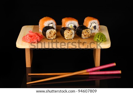 Tasty rolls served on wooden plate isolated on black - stock photo