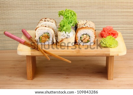 Tasty rolls served on wooden plate on wooden background - stock photo
