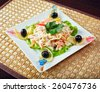 Tasty salad decorated with olives on skewers  - stock