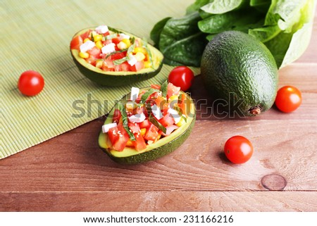 Tasty salad in avocado on table and bamboo napkin close-up - stock photo