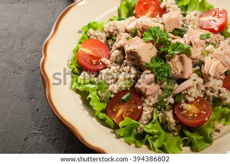 Tasty salad with couscous, tuna and vegetables on the plate - stock photo