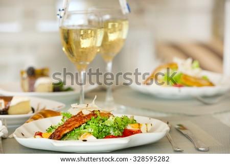 Tasty salad with served wine - stock photo