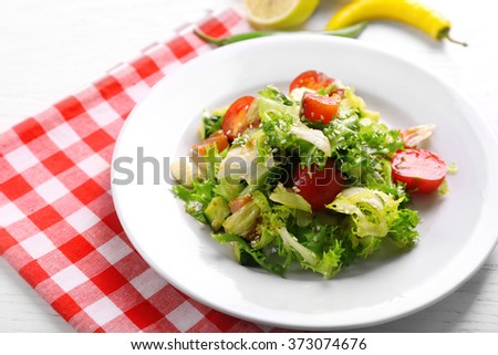 Tasty salmon salad on light wooden background - stock photo