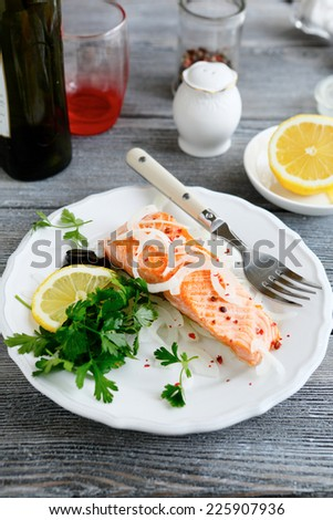 Tasty salmon with lemon on a plate, top view