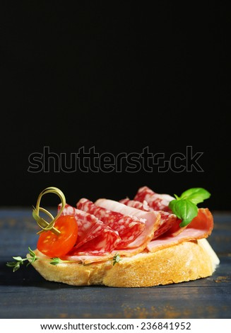 Tasty sandwich on wooden table, on black background - stock photo