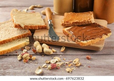 Tasty sandwiches with peanut butter on wooden board