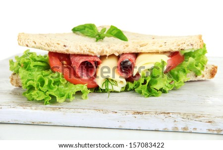 Tasty sandwiches with salami sausage and vegetables on cutting board, isolated on white