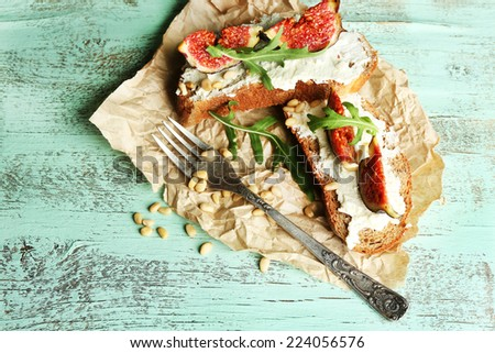 Tasty sandwiches with sweet figs and cottage cheese on wooden table - stock photo