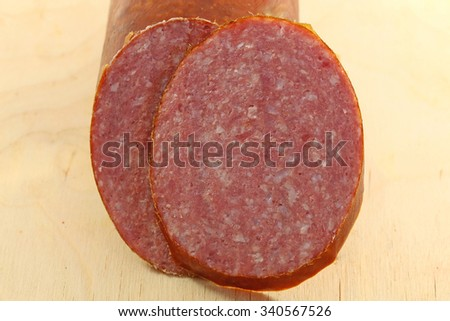 Tasty sausage meat on a wooden board photographed close up - stock photo