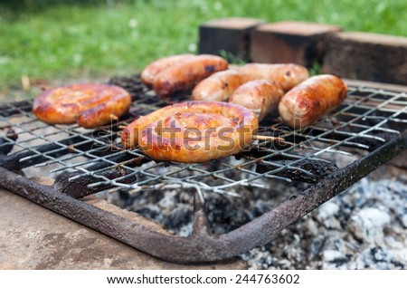 Tasty sausages cooking over the hot coals on a barbecue fire outdoors - stock photo