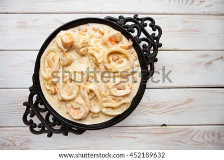 Tasty seafood in white sauce on a metal black plate. Top view - stock photo
