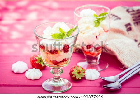 Tasty servings of strawberry pavlova in elegant glasses with meringues, cream, ice cream and fresh strawberries served for dessert on a pink wooden picnic table - stock photo