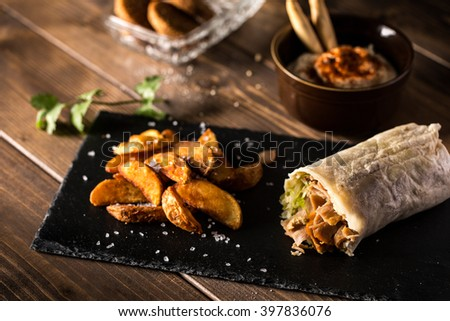 Tasty shawarma with fried potato on served wooden table - stock photo