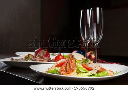 Tasty shrimp salad with vegetables on christmas table - stock photo