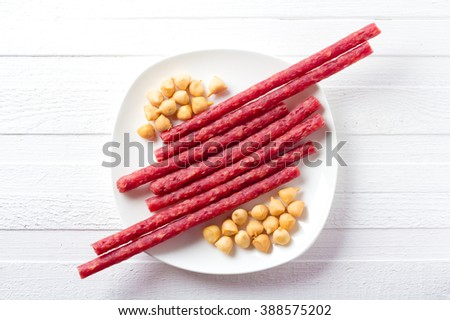 Tasty snacks to drinks - smoked sausage and smoked cheese on a round white plate. - stock photo