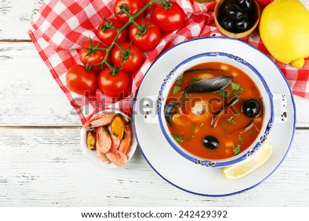 Tasty soup with shrimps, mussels, tomatoes and black olives in bowl on wooden background - stock photo