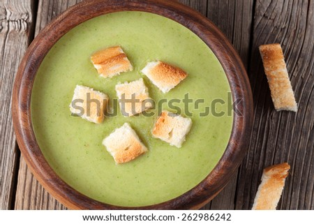 Tasty spinach green cream soup in a bowl with croutons on wooden vintage background - stock photo