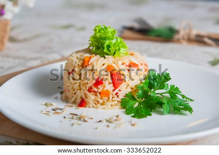 Tasty Steamed rice with vegetables decorated with lettuce and parsley on the white plate on served in eco style restaurant table - stock photo