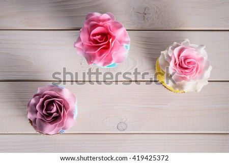 Tasty still life made of three colorful cupcakes with special eatable roses on the top. Shot from the upper angle. Seductive petals of flowers are perfect for decoration of confectionery. - stock photo