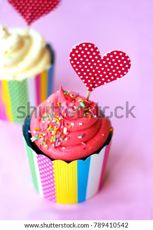 Tasty strawberry cupcake with red heart topper pink background. Valentine background