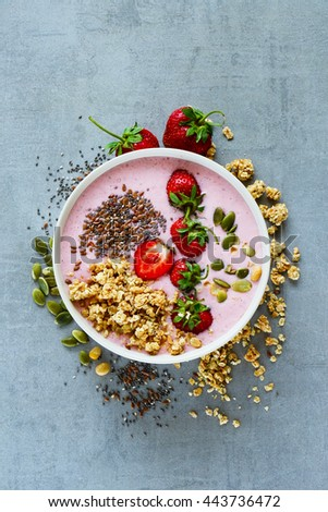 Tasty strawberry smoothie bowl with fruits, cereals, seeds and nuts over light grey background, top view. Healthy food for breakfast and snack - stock photo