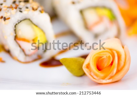 Tasty sushi rolls on a plate with ginger and wasabi decoration selective focus - stock photo