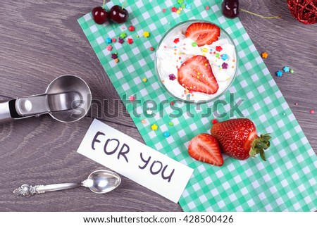 """Tasty sweet berry ice cream dessert in the glass and Ice cream spoon with ripe strawberries on the paper green napkin on the gray wooden table. """"For you"""" note on the paper. Candies with ice cream - stock photo"""