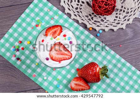 Tasty sweet ice cream dessert in the glass and Ice cream spoon with ripe strawberries on the paper green napkin on the gray wooden table. Candies with ice cream in sundae - stock photo