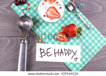 """Tasty sweet ice cream dessert in the glass and Ice cream spoon with ripe strawberries on the paper green napkin on the gray wooden table. """"Be happy"""" note on the paper list.  - stock photo"""