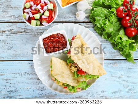 Tasty taco with tomato dip on plate and vegetables on table close up - stock photo