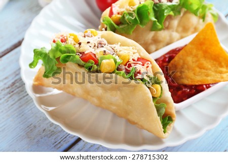 Tasty taco with tomato dip on plate on table close up