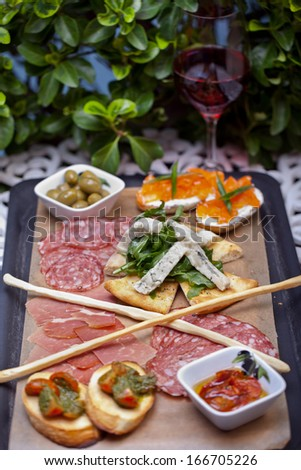 Tasty tapas appetizers on the table served with wine - stock photo