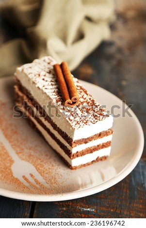 Tasty tiramisu cake on plate, on wooden table - stock photo