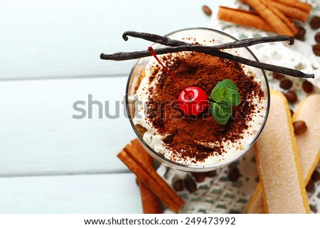 Tasty tiramisu dessert in glass, on napkin, on wooden background - stock photo