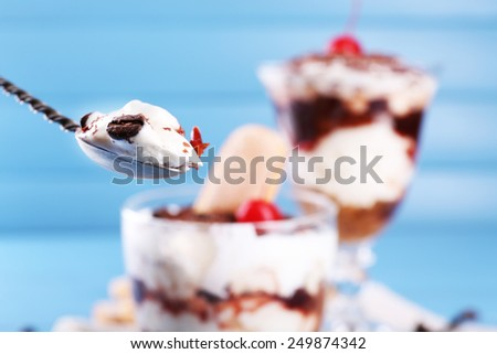 Tasty tiramisu dessert in spoon and glass, on color wooden background