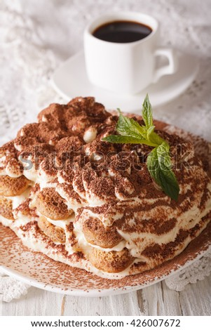 Tasty tiramisu on a plate and espresso coffee on a table close-up. vertical - stock photo