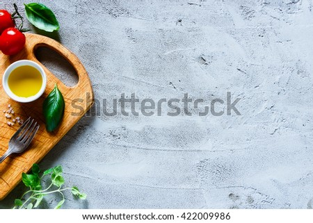 Tasty tomatoes with fresh basil leaves and olives oil on rustic wooden chopping board over concrete textured background, space for text. Italian food cooking ingredients. - stock photo