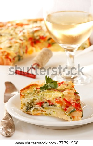 Tasty vegetables pie on a plate and glass of wine.