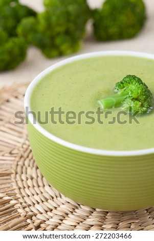 Tasty vegetarian broccoli soup recipe in a green bowl on vintage background - stock photo