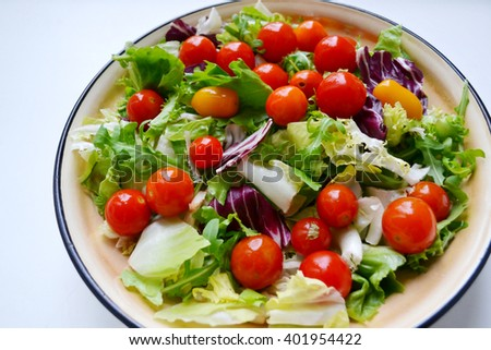 Tasty vegetarian salad with red and yellow cherry tomatoes, arugula, cabbage and lettuce - stock photo