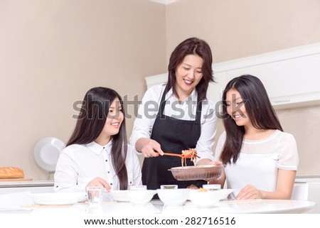 Tasty view. Asian mommy feeding her daughters at home - stock photo