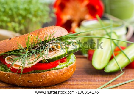 Tasty wholemeal bagel/burger with green pesto, fresh vegetables, dill and vegan sausage. Selective focus. - stock photo