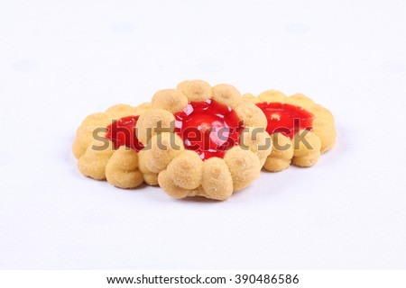 Tasty yellow baked cookies with red berry jam on the white cloth in restaurant or cafeteria - stock photo