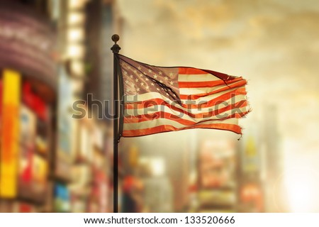Tattered American flag blowing in the wind against cool city blurred background - stock photo