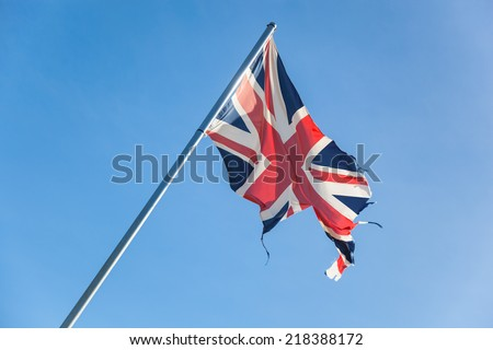 tattered british flag in front of the blue sky. Concept for separatism or collapse of Great Britain - stock photo