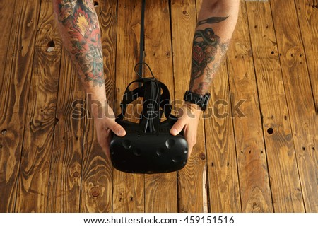 Tattoed hands hold virtual reality goggles, presentation of new technology, isolated on rustic wooden background in center