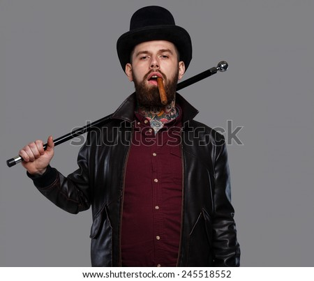 Tattoed male in hat and cigar holding cane - stock photo