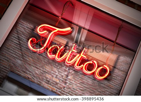 Tattoo sign, neon sign in a tattoo shop window. Red information sign, view from outside into a store.