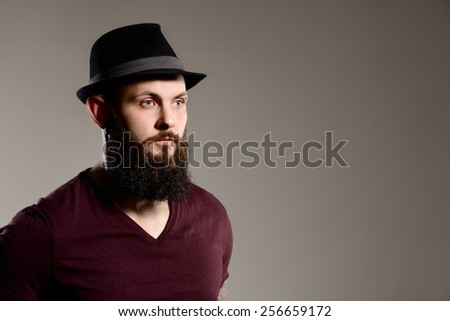 Tattooed bearded hipster guy - gray background - stock photo